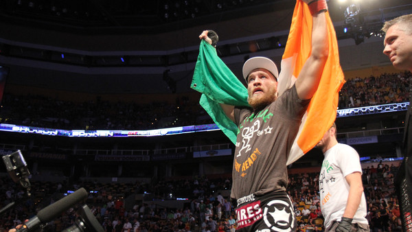 Conor McGregor, of Ireland, leaves the ring draped in an Irish flag after beathing Max Holloway in their UFC on Fox Sports 1 mixed martial arts bout in Boston, Saturday, August 17,2013. McGregor won via unanimous decision. (AP Photo/Gregory Payan)