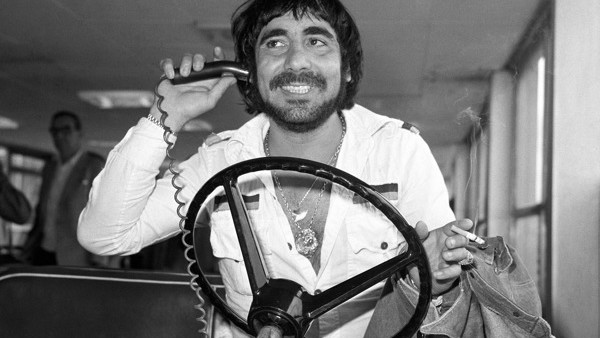 Keith Moon, drummer for the pop band The Who, at London's Heathrow Airport, takes the wheel of an airport luggage transporter. He was flying in from LA to join the group for a tour of England and France.