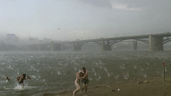 In this photo taken on a smartphone on Saturday, July 12, 2014, people run to shelter from hailstorm on the beach at Ob River, the major river in western Siberia in Novosibirsk, Russia. The Investigative Committee said in a statement published online Mond