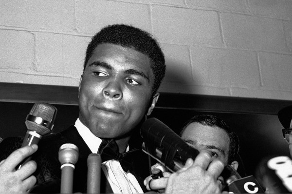 ADVANCE FOR USE SUNDAY, FEB. 23, 2014 AND THEREAFTER - FILE - In this March 29, 1966 file photo, reporters surround Muhammad Ali at Toronto's Maple Leaf Gardens after he won a unanimous decision over Canadian George Chuvalo. (AP Photo)