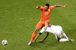 Netherlands' Memphis Depay falls over Costa Rica's Bryan Ruiz during the World Cup quarterfinal soccer match between the Netherlands and Costa Rica at the Arena Fonte Nova in Salvador, Brazil, Saturday, July 5, 2014. (AP Photo/Themba Hadebe)