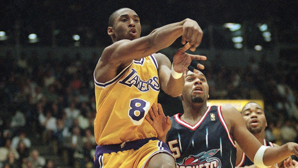 Los Angeles Laker guard Kobe Bryant (8) passes to a teammate under the basket as Houston Rockets, Sam Mack looks on during the first half at the Forum in Inglewood, California on Friday, March 7, 1997. (AP Photo/E. J. Flynn)
