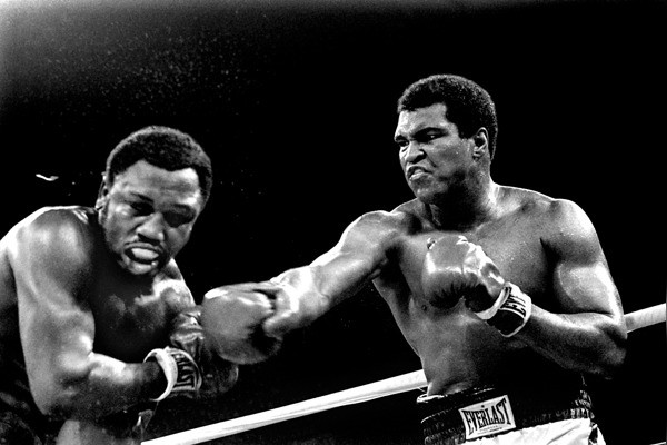 Spray flies from the head of challenger Joe Frazier as heavyweight champion Muhammad Ali connects with a right in the ninth round of their title fight in Manila, Philippines, October 1, 1975. Ali won the fight on a decision to retain the title. (AP Photo/
