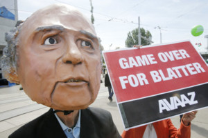 A protester wearing a mask depicting FIFA President Sepp Blatter stands in front of the building where the 65th FIFA congress takes place in Zurich, Switzerland, Friday, May 29, 2015. Protesters from the global campaign movement Avaaz demand the resignati