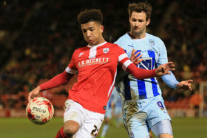Barnsley's Mason Holgate (left) and Coventry City's Nick Proschwitz battle for the ball.