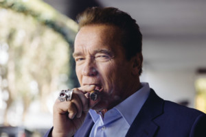 In this Sunday, March 22, 2015 photo, Arnold Schwarzenegger smokes a cigar during press day for
