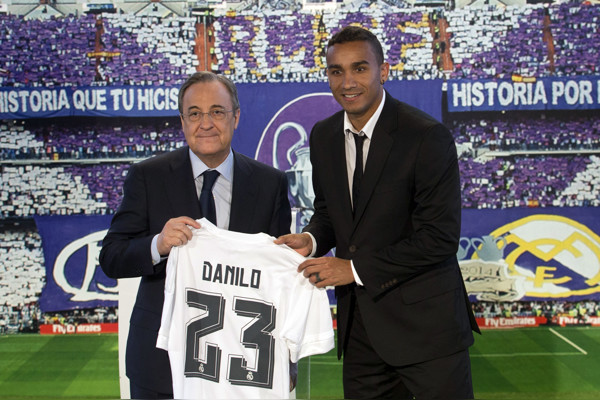 Real Madrid's new signing Danilo, right, displays his new shirt alongside club president Florentino Perez during his presentation at the Santiago Bernabeu stadium in Madrid, Spain, Thursday, July 9, 2015. Brazilian defender Danilo previously played fo