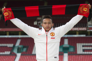 Manchester United's new player Memphis Depay poses for photographs at Old Trafford Stadium, Manchester, England, Friday July 10, 2015. The 21 year old Dutch international recently joined his Manchester United teammates for the first time since his mov