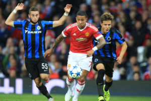 Manchester United's Memphis Depay (centre) battles for the ball against Club Brugge's Tuur Dierckx (left) and Dion Cools (right).
