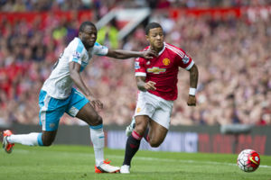 Manchester United's Memphis Depay, centre, fights for the ball against Newcastle's Chancel Mbemba during the English Premier League soccer match between Manchester United and Newcastle at Old Trafford Stadium, Manchester, England, Saturday, Aug. 2