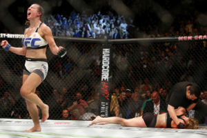 Miesha Tate, left, celebrates victory over Holly Holm in their UFC 196 womens bantamweight mixed martial arts match, Saturday, March 5, 2016, in Las Vegas. (AP Photo/Eric Jamison)